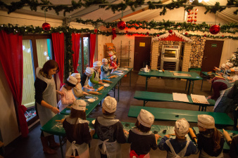 Children are kneading the dough in the eco-bakery, dressed in apron and hat.