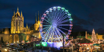 Illuminated big wheel at the market. In the background are the St. Mary's Cathedral and the Church of St. Severus