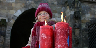 Girl lighting candles on the advent crown