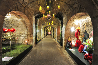 big yellow candles lighten the corridor of the vault, which is decorated with greenery, moss and christmas bags