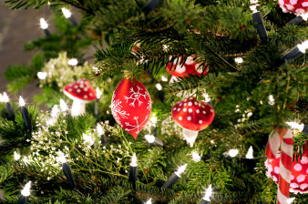 Close up of an illuminated Christmas tree with red and white decoration such as baubles, candy canes and mushrooms.