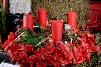 four red candles arranged on greenery and red paper, decorated with candy canes, fir cones and roses