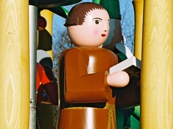 shaped, painted wooden figure with brown robe and an open book