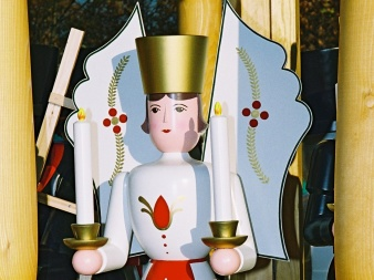 shaped, painted, wooden figure in white, red robe with big wings and two candles in the hand