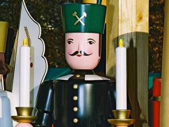 shaped, painted, wooden figure in miner´s uniform with two candles in the hand