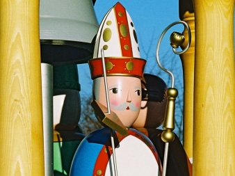 shaped, painted wooden figure with pierced book, sceptre and hat