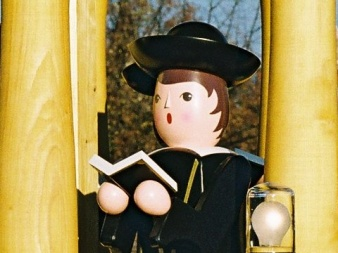 shaped, painted wooden figure with black robe, hat and open book.