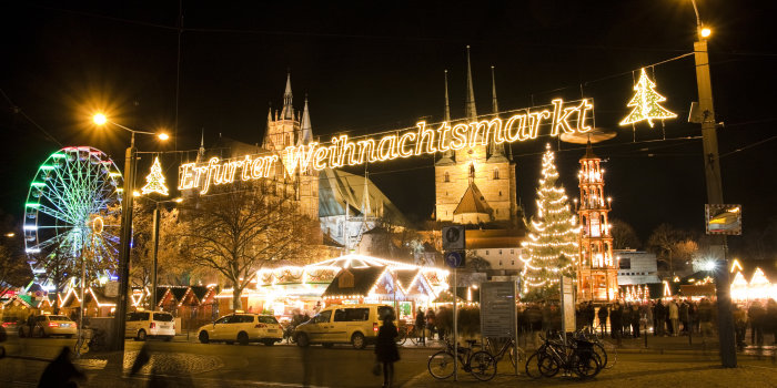 The focus is on the illuminated lettering Erfurt Christmas Market. In the background are the cathedral and some attractions as the big wheel and the Christmas pyramid.